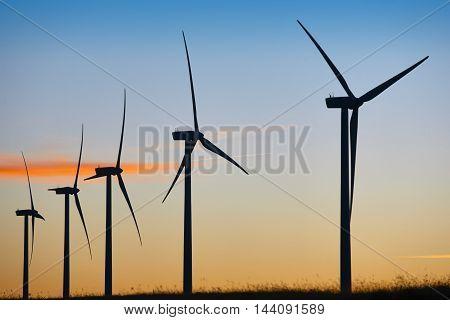 Wind turbines at sunset. Clean alternative renewable energy. Horizontal