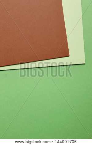 Colored cardboards background in green brown tone. Copy space. Vertical