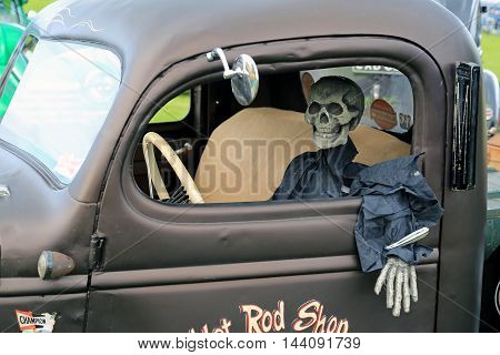 ALAHARMA, FINLAND - AUGUST 12, 2016: Skeleton clothed in black sits comfortably behind the wheel of a pick-up truck with hand under the exterior door handle. A funny detail of a retro GMC truck displayed on the annual trucking event Power Truck Show 2016.