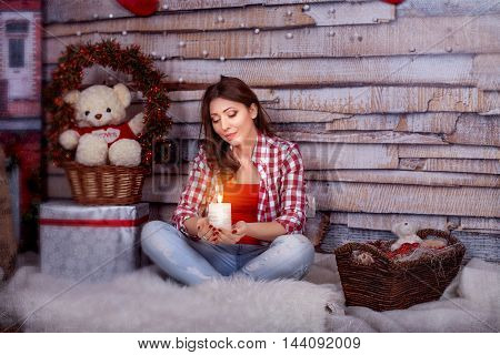 beautiful young girl holding a candle. The concept of New Year and Merry Christmas