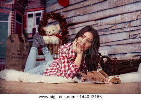 beautiful young girl reading a book. The concept of New Year and Merry Christmas