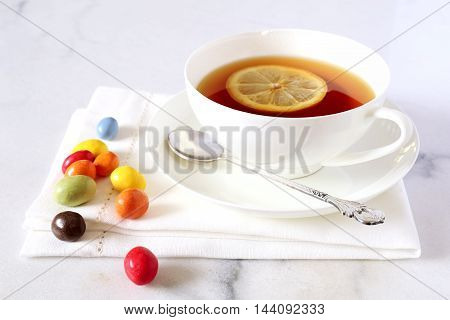 Cup of tea with lemon and multicolored chocolate drops