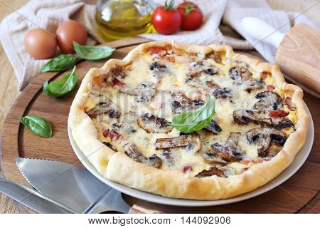 Mushrooms and bacon quiche, intact on wooden cutting board