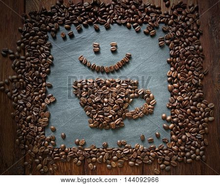 Cup of coffee and smiley face from coffee beans. Heap of coffee bean in form of cup on grey stone surface texture and wooden table. Coffee shop or cafe background. Soft color toning, top view