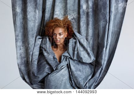 Young beautiful african girl posing, wrapping up  in grey cloth. Copy space.