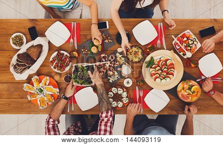 People eat healthy meals at festive table served for party. Friends celebrate with organic food on wooden table top view. Woman pass dish to man