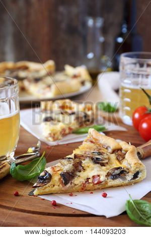 Mushrooms and bacon quiche and two mugs of beer
