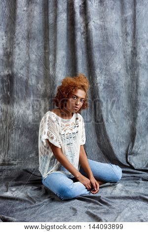 Young beautiful african girl looking at camera, sitting at floor over grey cloth background. Copy space.