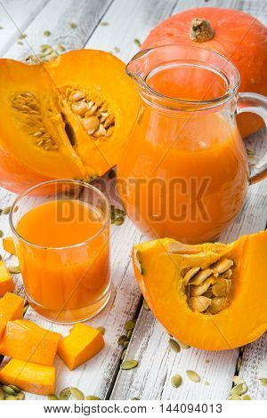 fresh orange pumpkin and pumpkin juice on a white wood background rustic style selective focus