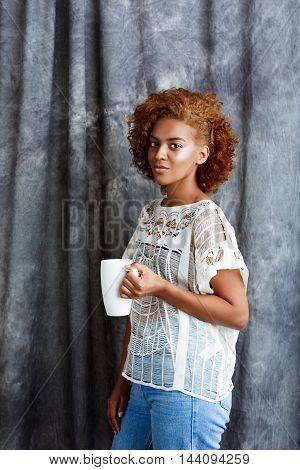 Young beautiful african girl smiling, looking at camera, holding cup, posing over grey cloth background.  Copy space.