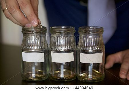 Three jars - piggy bank. In the miscellaneous expenses. They are glued to the tape to write her goal of spending. A man puts a coin in a piggy bank. At the bottom poured a bit of coins. Budget Management.