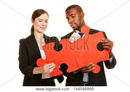 Man and woman connecting two big oversized red jigsaw puzzle pieces