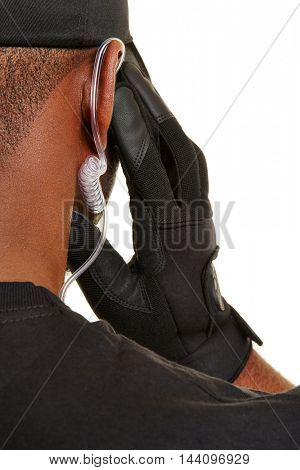 Security guard holding hand to headset in his ear