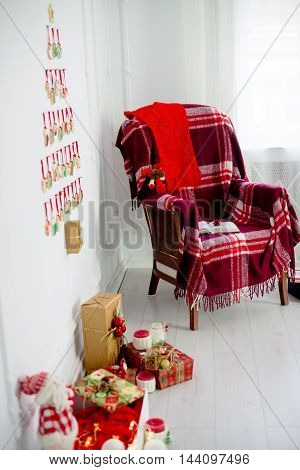 Christmas decorations. a comfortable armchair with a rug gifts Christmas Tree Christmas cookies laid out on a white wall