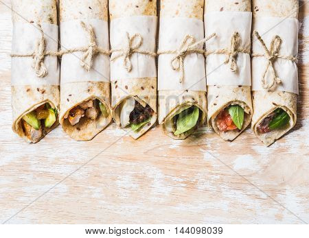 Tortilla wraps with various fillings on shabby painted board over white wooden background, top view, copy space, horizontal composition. Healthy snack or take-away lunch bites