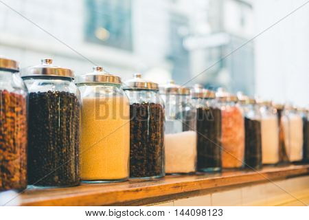 Jars of coffee beans instant coffee sugar and ingredients in vintage tone depth of field effect with copy space