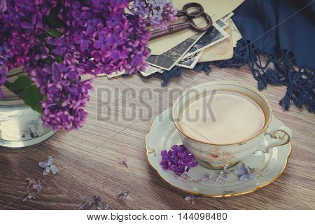 summer tea time - cup of tea with lilac and vintage photos, retro toned
