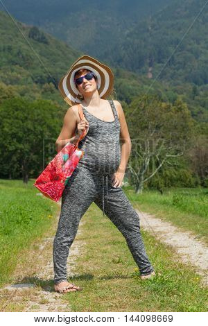 Beautiful pregnant woman with bag and hat, outdoors