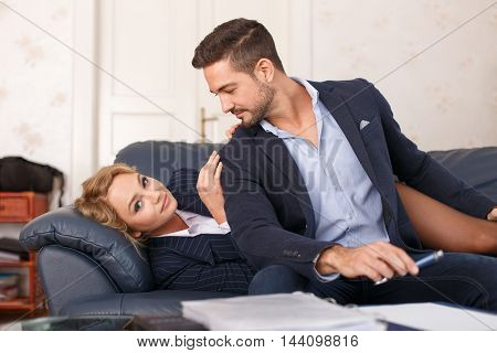 Young businessman and businesswoman get into hot situation on sofa