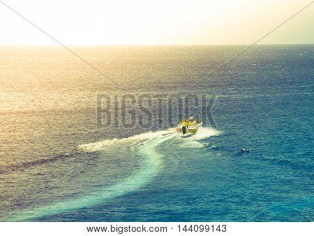 Man in Motorboat crossing ocean at sunset