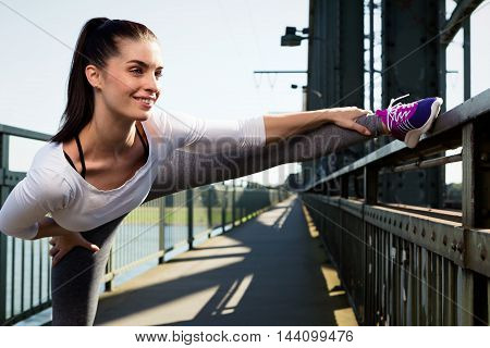 young woman streching before sports. urban style