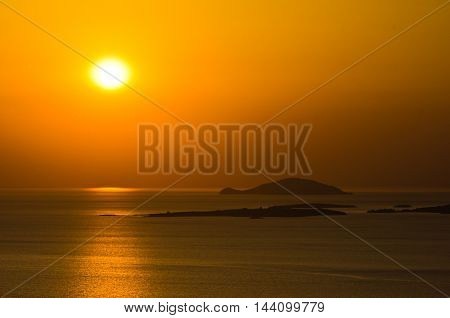 Sunset at sea, with small greek islands in background, Sithonia, Greece