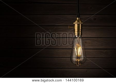 Close up of a vintage, Edison lightbulb over wooden background with copy space