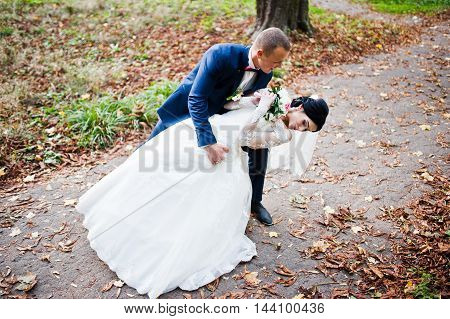 Dancing Wedding Couple At Autumn Path On Park