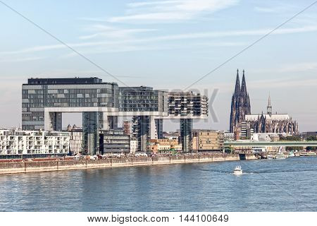 COLOGNE GERMANY - AUG 7 2016: Crane Houses at the Rhine river in Cologne. Cologne cathedral in the background. North Rhine-Westphalia Germany