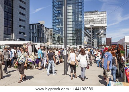 COLOGNE GERMANY - AUG 7 2016: Crowded waterfront promenade at the Rheinauhafen in the city of Cologne Germany
