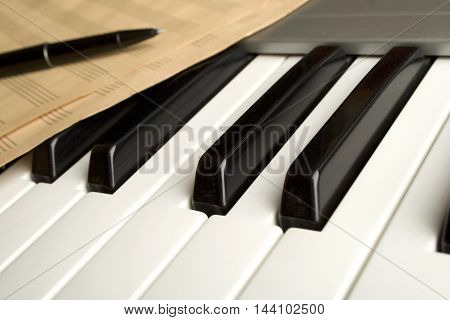 Brown wooden piano with music books and manual