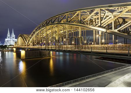 The Hohenzollern bridge and Cologne cathedral illuminated at night. Cologne North Rhine-Westphalia Germany