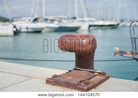 Rusted Mooring Bollard  With Sailing Boat In Background