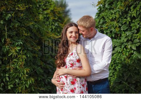 Young pregnant woman with husband walking in the park