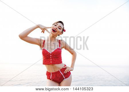 Happy pretty pinup girl in red swimsuit showing victory sign while standing at the beach