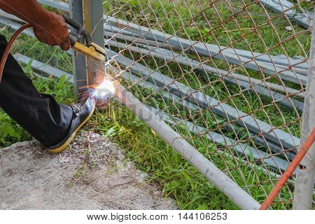 Welder working a welding metal. Not wearing the glove causing a danger: Select focus welding steel with shallow depth of field :