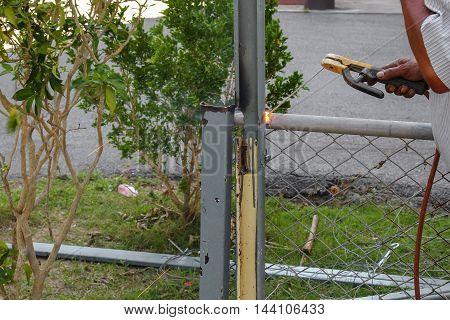 Welder working a welding metal outdoor. Not wearing the glove causing a danger: