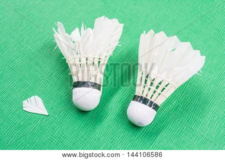 Two used white badminton shuttlecocks on a green court.