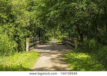 A bike trail crossing a bridge in the summer.