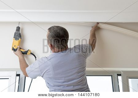 Worker Drilling Ceiling for Curtain Rail