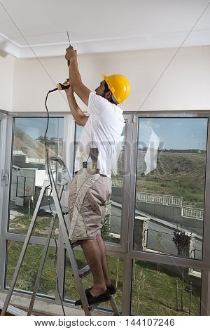Vertical image of manual worker drilling hole in ceiling for curtain rail.