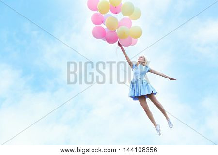 Beautiful young woman holding air balloons