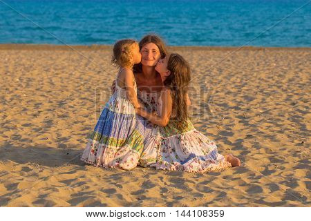 Children kissing and hugging mother at the beach. Happy family concept.