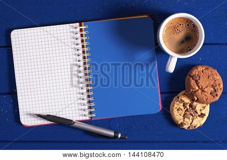 Opened notebook coffee cup and cookies on a dark blue background top view