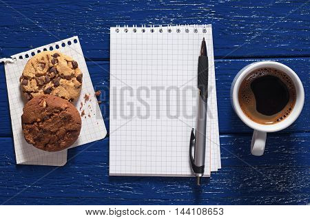 Opened notebook cup of hot coffee and cookies on a dark blue background top view