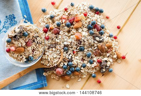 Serving Muesli Scattering Of Wild Berries, Nuts On Wooden Table