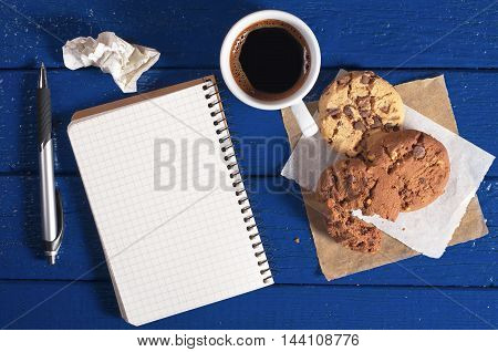 Notepad with empty page coffee cup and chocolate cookies on a dark blue desk top view. Space for your text