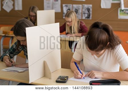 Four pupils write a test in the classroom