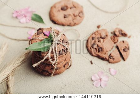 Pile of chocolate chip cookies tied with a rope on rustic grey table