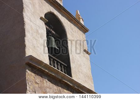 This is an image of a California Mission bell tower and bell taken under clear blue sky on a sunny day.